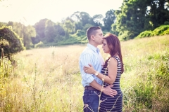 Engaged couple kissing in field